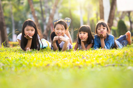 Les petites filles asiatiques portant sur l'herbe verte sous la lumière du soleil Banque d'images - 55488189