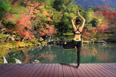 秋または秋の公園で屋外若い女性トレーニング ヨガ