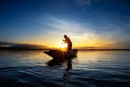 pecheur: pêcheur sur un lac du bateau au lever du soleil