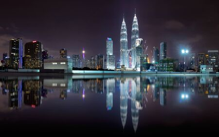 Night view of kuala lumpur city skyline with stunning reflection in water