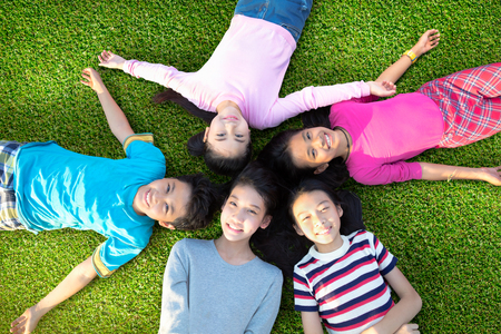 Smiling young boys and girls lying on green grass