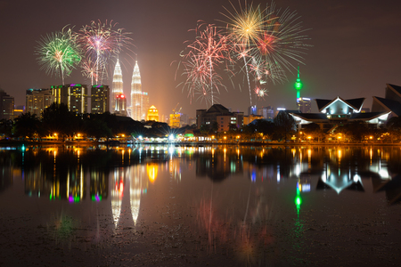 kuala lumpur tower: Night view of kuala lumpur city with fireworks and reflection in water