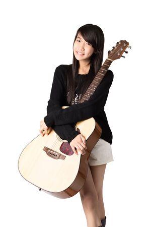 guitarra: Muchacha asiática joven que sostiene una guitarra acústica, aislado en blanco