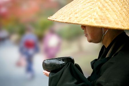 Closeup japanese monk praying and asking for donations, Kyoto Japan