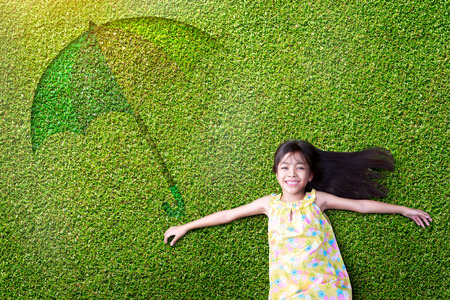 woman laying: Little asian girl resting on green grass
