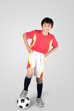 asian boy: Cute asian boy playing soccer, Isolated on grey background Stock Photo