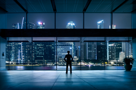 Businessman standing at night cityscape, Business vision concept photo