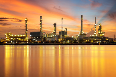 Petrochemical plant area in morning with reflection in river Imagens