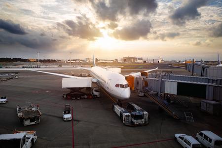 Avión cerca de la terminal de un aeropuerto en la puesta del sol, el aeropuerto internacional de Narita