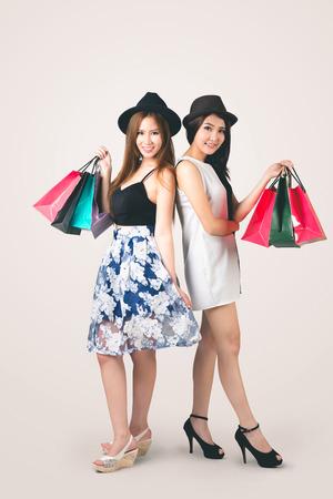 Beautiful asian teen girls carrying shopping bags, Vintage colour tone photo