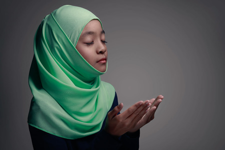 Young muslim girl praying, Isolated on grey background