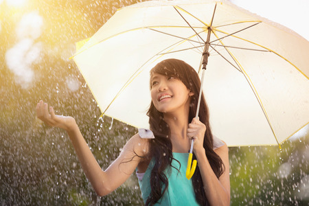 Portrait of beautiful young teen girl with umbrella under rain