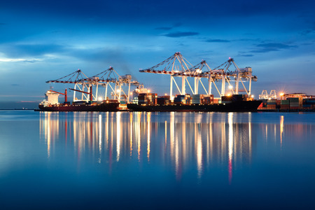 unloading: Containers loading by crane in the evening trade port shipping, Shipping and logistic concept