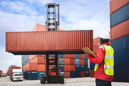 commercial docks: Foreman control loading containers box from cargo freight ship Stock Photo