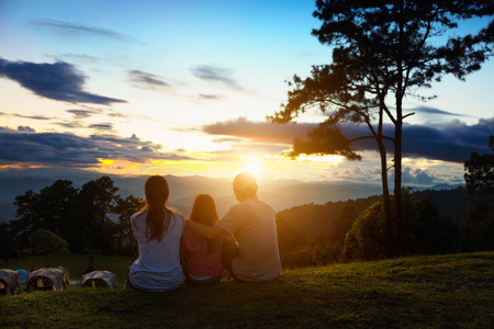 Asian family seat on the top of mountain and look at sunset, Family travel concept Stock Photo