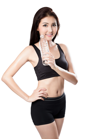 Excited young asian woman showing a bottle of water after doing sport, Isolated over white photo