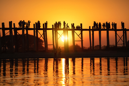 Silhouette of people traveling across the U Bein Bridge in the evening. Mandalay Myanmar Stock Photo