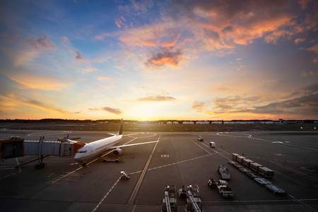 Airport runway with airplanes at beautiful sunset