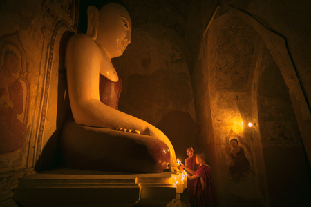 worship god: Little monk praying with candles in front of buddha statue inside old pagoda, Bagan Myanmar
