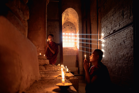 buddhist's: Novices praying with candles in front of buddha statue inside old pagoda, Bagan Myanmar