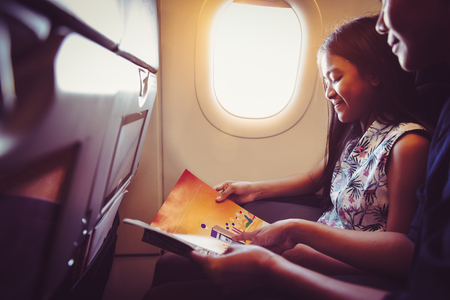 Mother with daughter sit on their place in airplane economy class and read a magazine