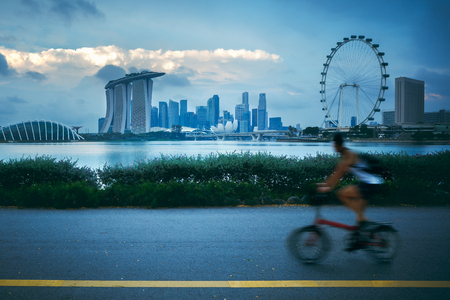 Fast moving cyclists at park with viewing of Singapore