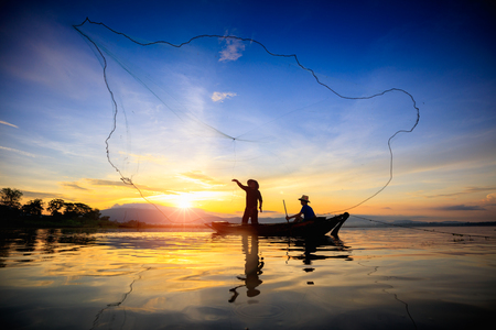 le: Silhouette of fishermen using nets to catch fish at the lake in the morning