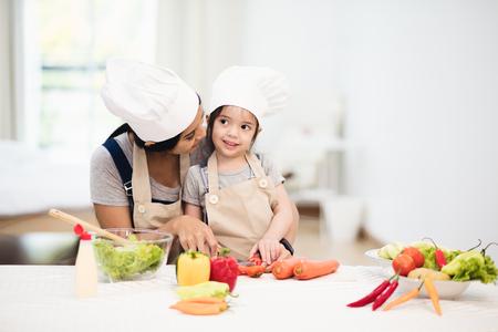 かわいい女の子とシェフの帽子に彼女のお母さんがカット野菜サラダを調理し、笑顔