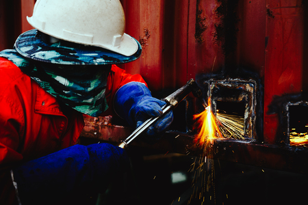 Closeup industrial Worker at the factory welding photo