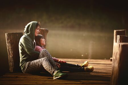 Mother and daughter sitting on the wooden bridge near the river photo