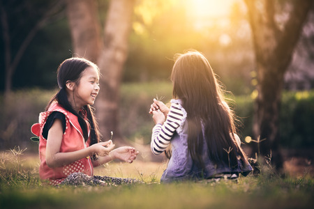 Two asian little girl playing together in a park with sunset photo