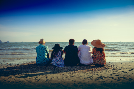 Traveler family sitting on beach photo