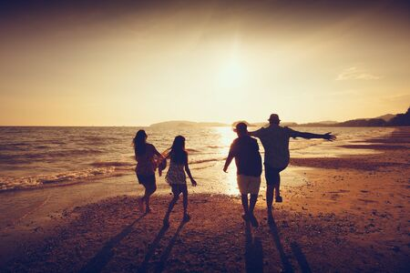 Asian family running on background of sunset beach and sea photo