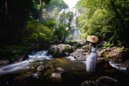 Young female traveler standing by a stream in the forest photo