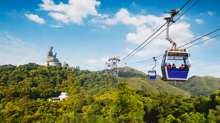 Ngong Ping cable car with big buddha statue in background, Hong Kong China