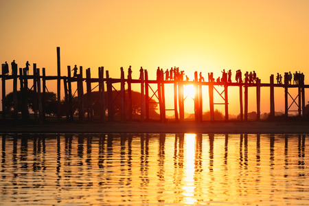 Silhouette of people traveling across the U Bein Bridge in the evening. Mandalay Myanmar Stock fotó