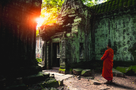 Buddhist monk at Angkor Wat ancient khmer architecture Ta Prohm temple ruins hidden in jungles, Cambodia