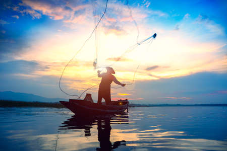 Silhouette fisherman throwing fishing net during sunrise Stockfoto