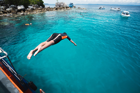 Teenage boy jumping off boat into the ocean, Trat Thailand