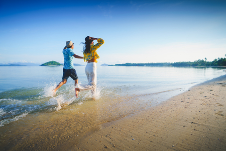 Happy middle aged couple running on a beach, Koh Mak Thailand Archivio Fotografico - 101520019