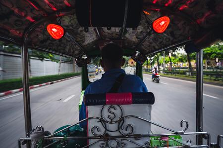 Tuk tuk driver speeding at night in Bangkok, Thailand.