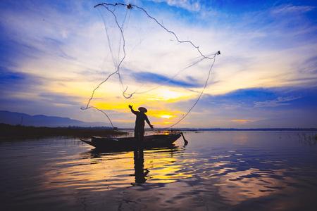 Silhouette fisherman throwing fishing net during sunrise Фото со стока