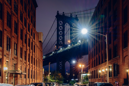 Brooklyn bridge seen from a narrow alley enclosed by two brick buildings at dusk, NYC USA