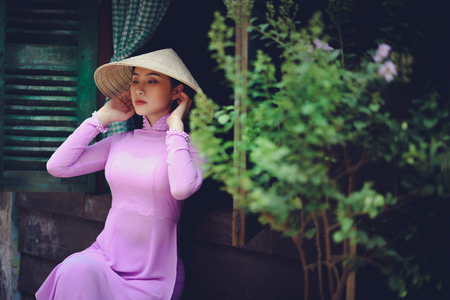 Beautiful vietnamese woman in Ao Dai traditional dress of Vietnam, Ho Chi Minh city Vietnam