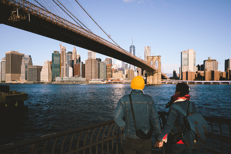 Asian couple holding hand at Brooklyn bridge, NYC USA