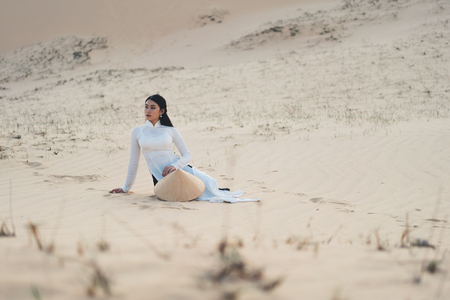 Beautiful vietnamese lady with vietnam culture traditional dress sitting at a white sand Mui ne, Ho Chi Minh City Vietnam