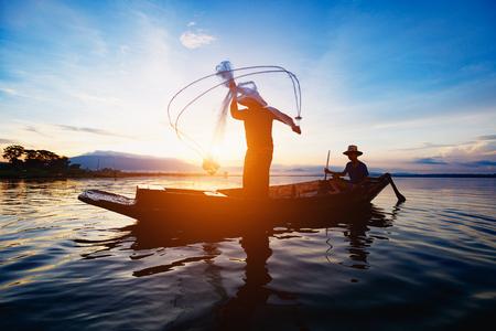 Schattenbild von den Fischern, die morgens Netze verwenden, um Fische am See zu fangen