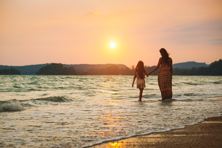 Mother and daughter walking on the beach with sunset, Krabi Thailand