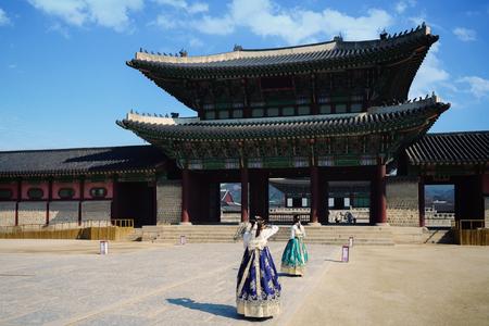 Female traveler in korean national dress or Hanbok traveling into the Gyeongbokgung Palace, Seoul South Korea Редакционное