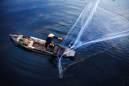 Asian fisherman on wooden boat casting a net for catching freshwater fish in nature river in the early morning before sunrise Standard-Bild